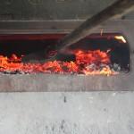 Das Feuer wird aus dem Backofen geräumt.